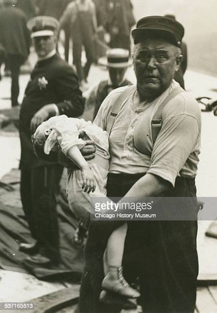 Chicago fireman Leonard E Olson carrying a child from the Eastland Disaster, Chicago, Illinois, 1915. He received the Lambert Tree Medal for his...