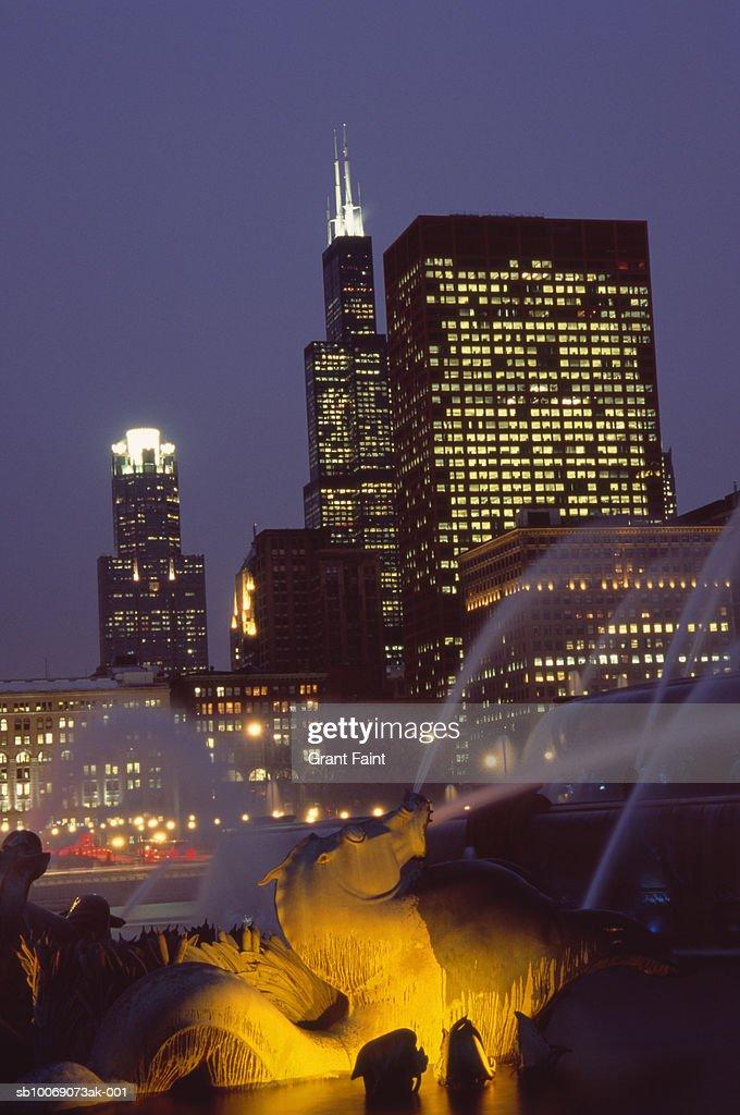USA, Chicago, fountain with skyline illuminated at dusk : Stockfoto