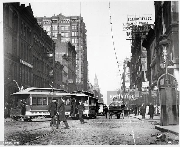 Chicago, IL- Trolleys and a horse and carriage are shown going up and down Madison Street at Fifth Avenue. Undated photograph.