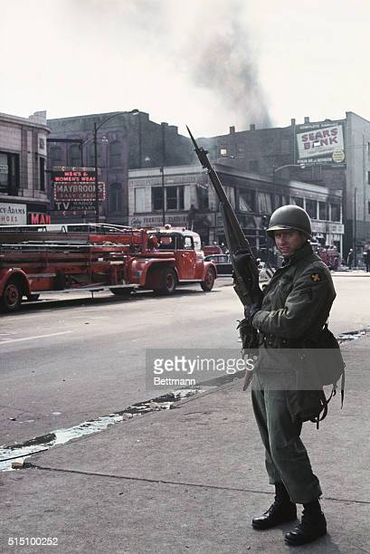 National guardsman stands alert as firemen battle blaze set by rioting Negroes following the death of Dr Martin Luther King Jrm April 4th