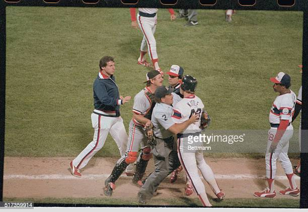 After being hit on the knee by a ball pitched by Orioles' Mike Flanagan White Sox outfielder Ron Kittle is restrained by plate Umpire Nick Bremigan...