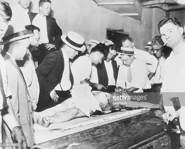 Crowds of the curious gather and stare at the body of John Dillinger as it lay on a rubber stretcher in the country morgue following his slaying by...