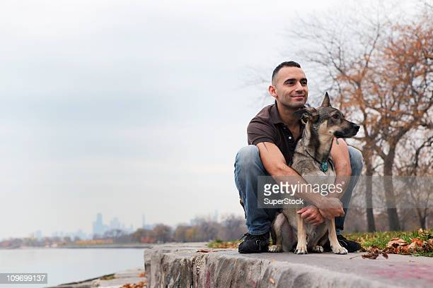 usa, chicago, lake michigan, smiling man hugging dog on ledge - chicago illinois stock pictures, royalty-free photos & images