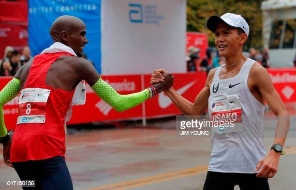Chicago Marathon winner Mo Farah of Britain greets Suguru Osako of Japan after he crosses the finish line in third place in Chicago October 7 2018...