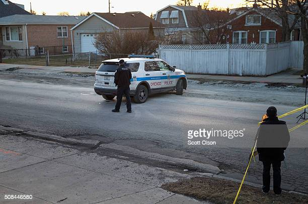 Chicago police officer guards the perimeter of a crime scene where six people were found slain inside a home on the city's Southwest Side on February...