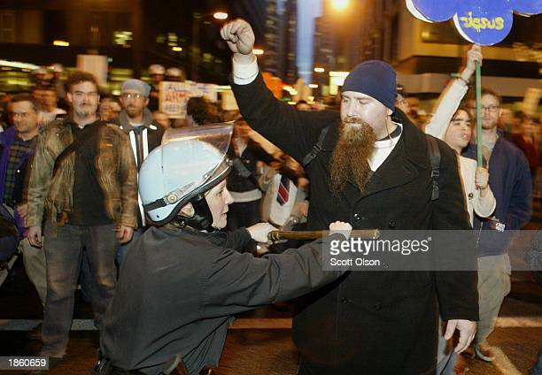 Chicago police officer holds a protestor back with her baton during an antiwar protest on March 20 2003 in Chicago Illinois Several thousand...
