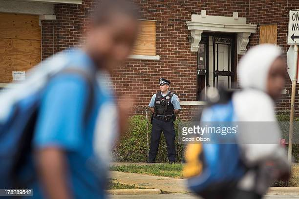 Chicago Police Officer John Bertetto stands outside a boardedup home while he watches students walk home from Laura Ward Elementary school on the...