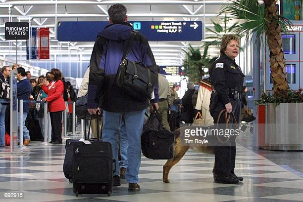 Chicago Police officer Karen Makowski and her Belgian Malinois patrol dog named Arco pause for a moment while working in the United Airlines terminal...