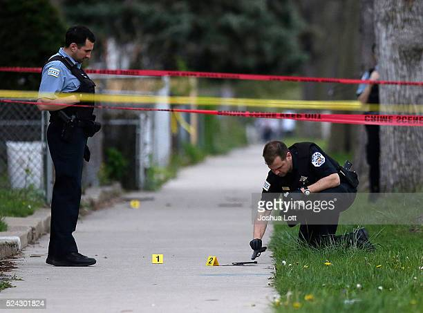 Chicago Police officer left watches as an evidence technician officer investigates a gun at the scene where a 16yearold boy was shot in the head and...