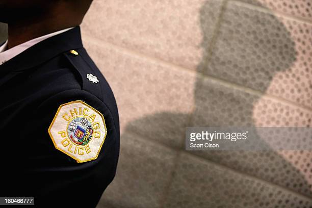 Chicago police officer listens as Mayor Rahm Emanuel discusses a plan to reassign 200 police officers from administrative duties back to patrol...