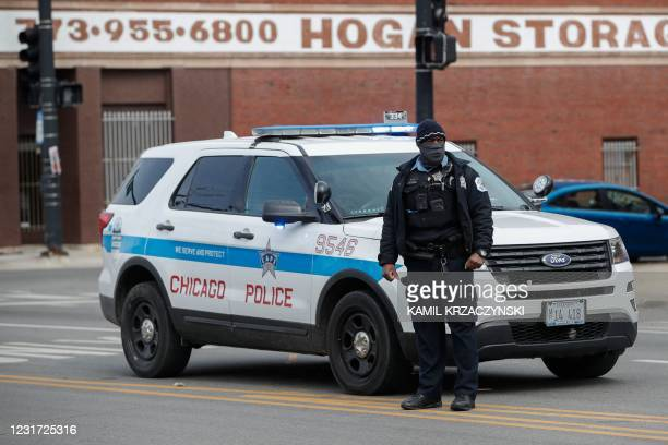 Chicago Police officer monitors the scene after a shooting in Chicago, Illinois, on March 14, 2021. - At least 15 people were shot, two of them...