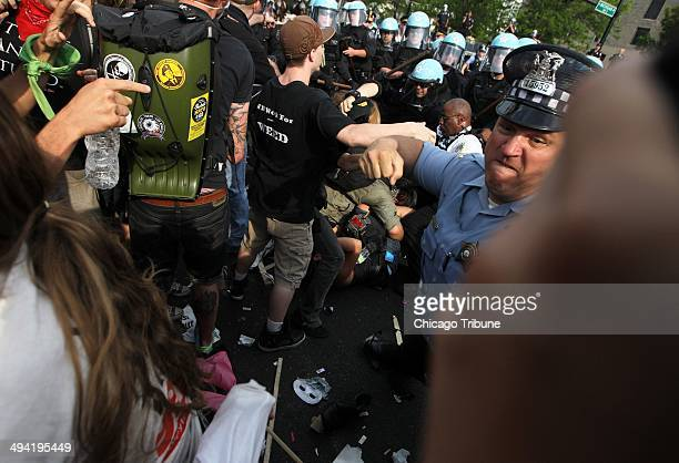A Chicago police officer punches an antiNATO protester who was hitting officers with a stick as the two groups clash at the end of their march at...