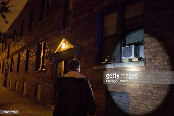 A Chicago Police officer shines a light on a wall at the scene of a fatal shooting in the 5900 block of West Thomas Street Friday June 16 in the...