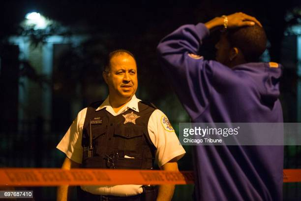 A Chicago Police officer speaks to a man at the scene where a man and woman both in their 60s were found stabbed to death in a home by a family...