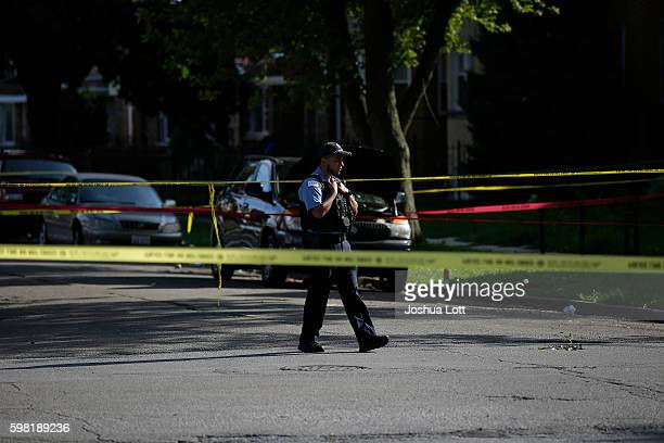 Chicago police officer stands at the crime scene of a fatal shooting where a man was shot in the head in the 7300 block of South Rockwell Street on...