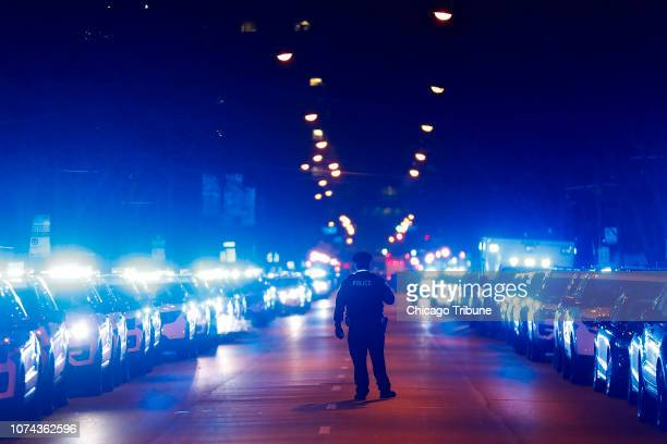 A Chicago police officer stands on the street following the procession carrying the bodies of Chicago police Officers Eduardo Marmolejo and Conrad...