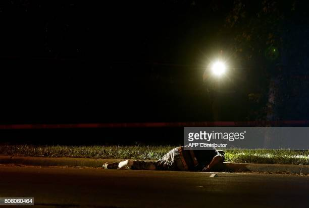 A Chicago Police officer uses his flashlight to investigate the crime scene where a man was shot and killed on the Near West Side on July 2 2017 in...