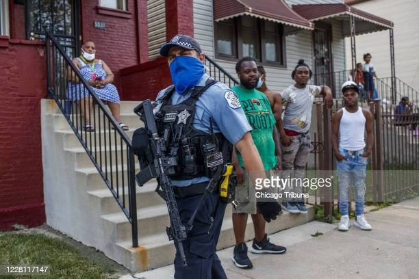 Chicago police officer with a rifle walks near the scene of a police-involved shooting in the Englewood neighborhood on Aug. 9, 2020. A police...