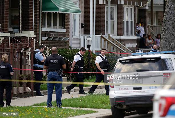 Chicago Police officers and evidence technicians investigate the scene where a 16yearold boy was shot in the head and killed and another 18yearold...