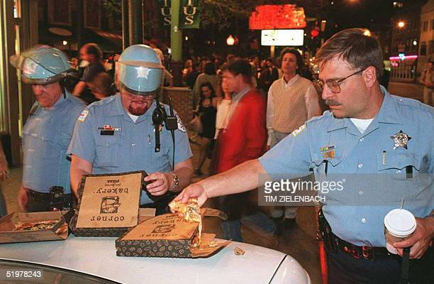 Chicago Police officers eat pizza during the third quarter of the Seattle SuperSonics' 8978 defeat of the Chicago Bulls in game 5 of the NBA finals...
