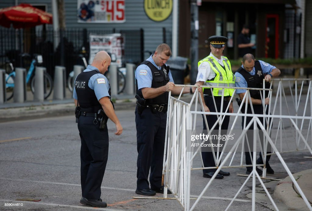Chicago Police officers put a gate in place along the route of the Chicago Marathon on October 8, 2017 in Chicago, Illinois. / AFP PHOTO / Joshua Lott