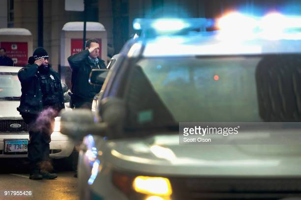 Chicago police officers salute as an ambulance carrying the remains of Cmdr Paul Bauer leaves Northwestern Memorial Hospital on February 13 2018 in...