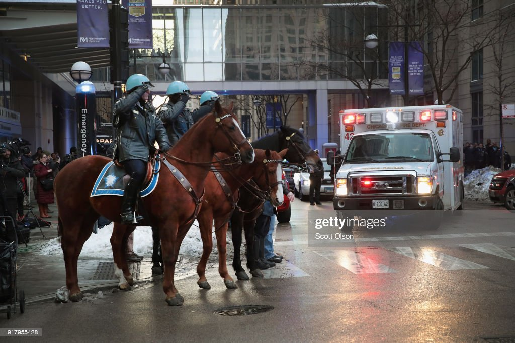 Chicago police officers salute as an ambulance carrying the remains of Cmdr. Paul Bauer leaves Northwestern Memorial Hospital on February 13, 2018 in Chicago, Illinois. Bauer, who was downtown leaving a training session, was shot while trying to help stop a man being pursued by tactical officers.