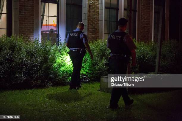 Chicago Police officers search bushes near the scene where a man and woman both in their 60s were found stabbed to death in a home by a family member...