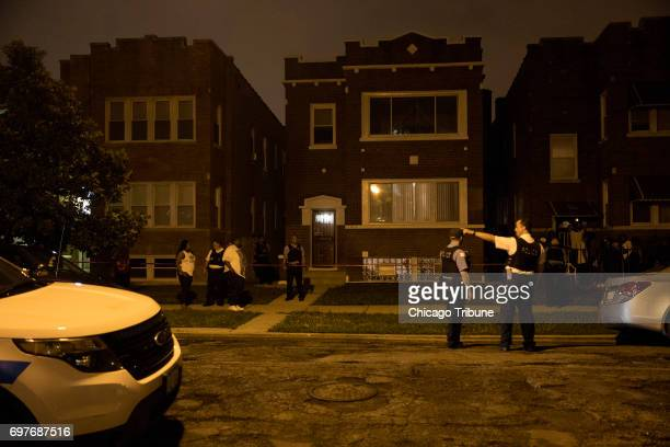 Chicago Police officers stand outside a house where a man and woman both in their 60s were found stabbed to death by a family member in the 1400...