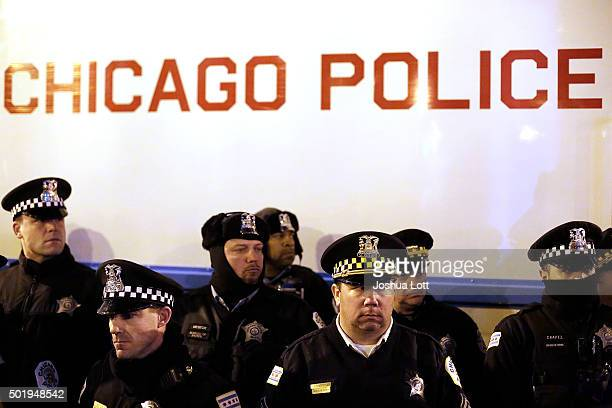Chicago police officers surround a police vehicle as they watch demonstrators protesting the fatal police shooting of Laquan McDonald December 18...