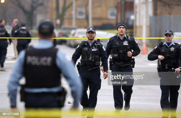 Chicago Police officers walk near the scene where four people were shot and killed at a restaurant in the 2700 block of East 75th Street on March 30...