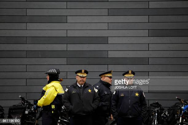 Chicago police officers watch as demonstrators protest outside the Chicago Water Tower on April 2 2018 in Chicago Illinois in response to the police...