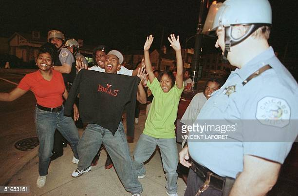 Chicago police watches fans celebrate early 14 June after the Chicago Bulls beat the Utah Jazz in game six of the NBA Finals by a score of 9086 to...