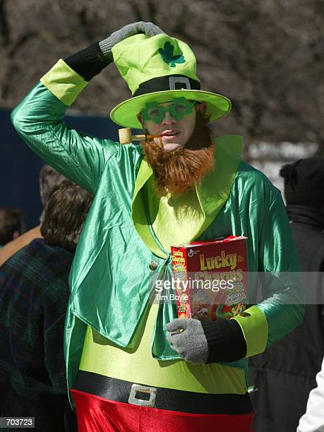Chicago resident Rory O''Conner holds onto his hat and a box of Lucky Charms cereal March 16 2002 as he marches in Chicagos St Patricks Day parade US...