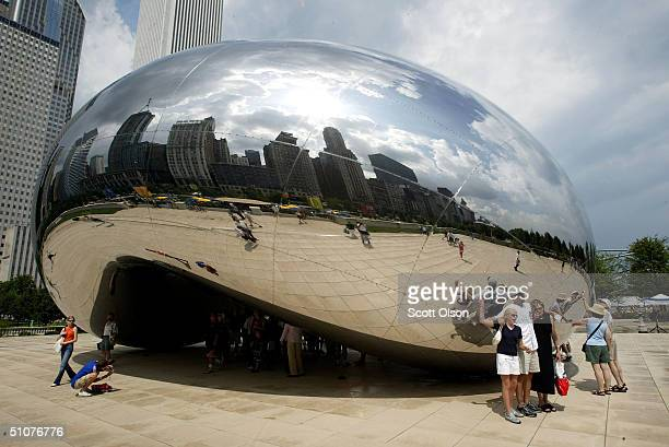 Chicago residents and tourists explore the Cloud Gate sculpture by Anish Kapoor in the newly opened Millennium park July 16 2004 in Chicago Illinois...