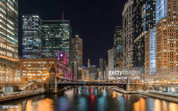 Chicago River Amidst Illuminated Buildings In City At Night