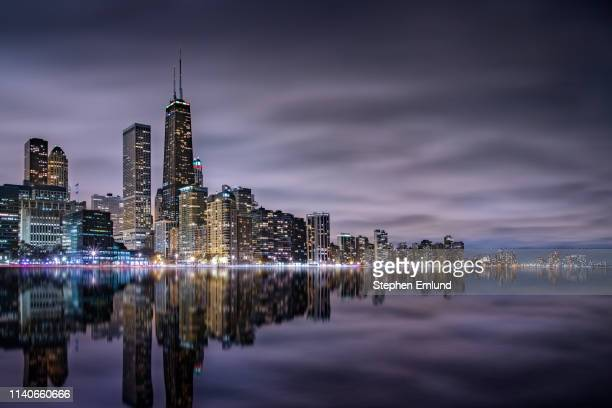 chicago skyline and lake michigan at night - chicago stock pictures, royalty-free photos & images