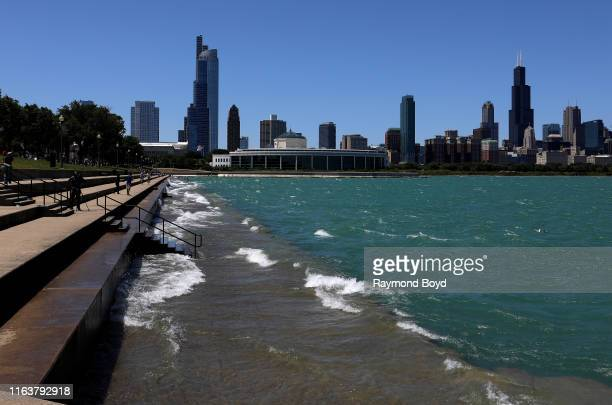 Chicago skyline, as high winds continue to push the waters of Lake Michigan over the top of the pedestrian and bike trail along the lakefront in...