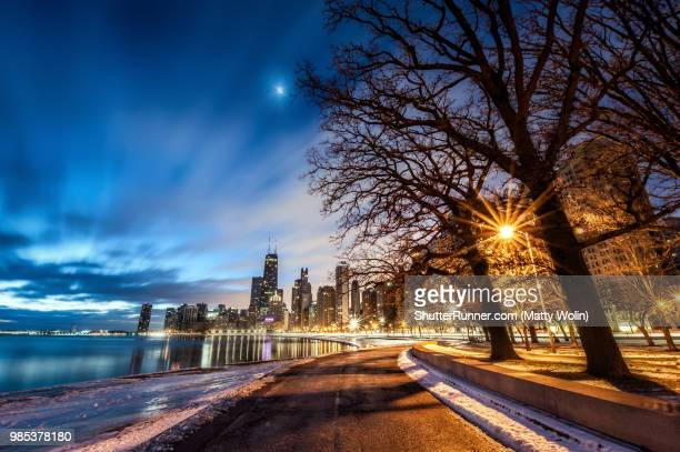 chicago skyline from the lake shore path at night - chicago illinois stock pictures, royalty-free photos & images