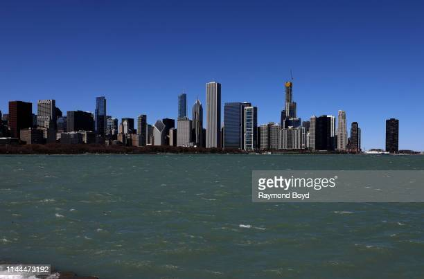 Chicago Skyline with high winds causing Lake Michigan's water to flow over the break wall along the lakefront in Chicago, Illinois on April 20, 2019.