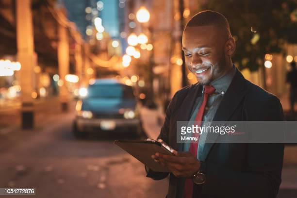 Chicago Streets at Night Smiling Businessman with Tablet Computer