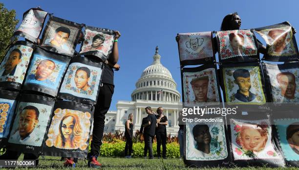 Chicago student London Strong holds up images of victims of gun violence that are part of the Faces Not Forgotten project during the National Rally...
