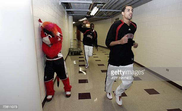 Switzerland's Thabo Sefolosha and teammates Luol Deng run past mascot 'Benny the Bull' 09 December 2006 before their game against the Minnesota...