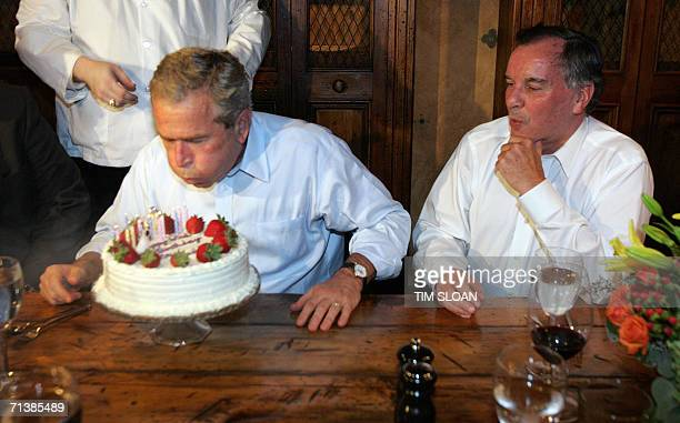 Chicago, UNITED STATES: US President George W. Bush blows out the candles on his birthday cake beside Chicago Mayor Richard M. Daley during a private...