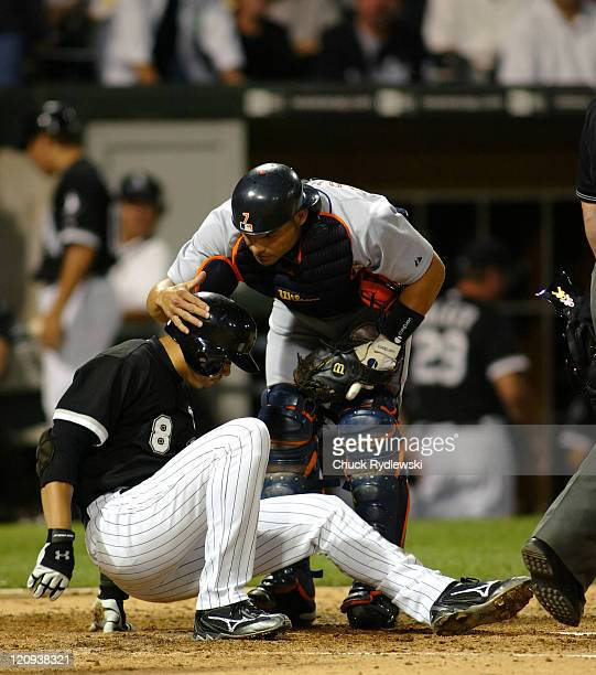 Chicago White Sox' 2nd Baseman Alex Cintron is consoled by Pudge Rodriguez after Rodriguez tagged him out at homeplate during the game against the...