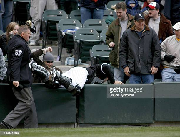 Chicago White Sox' Catcher AJ Pierzynski tumbles into the stands trying to catch a foul pop during their game against the Minnesota Twins April 7...