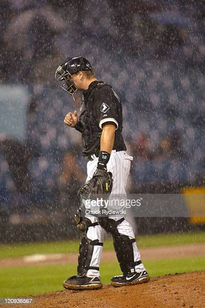 Chicago White Sox' Catcher, A.J. Pierzynski, waits for Manager, Ozzie Guillen, to change pitchers in a driving rain during their 12-5 loss to the the...
