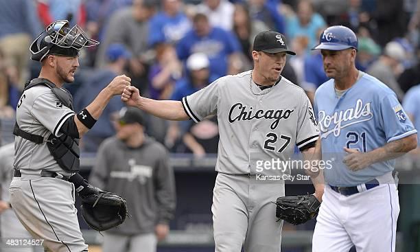Chicago White Sox catcher Tyler Flowers and relief pitcher Matt Lindstrom congratulate each other as Kansas City Royals third base coach Dale Sveum...