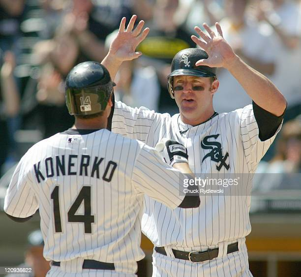 Chicago White Sox' DH/1B Jim Thome greets teammate Paul Konerko at home plate after Konerko's 2 run homer tied their game against the Toronto Blue...