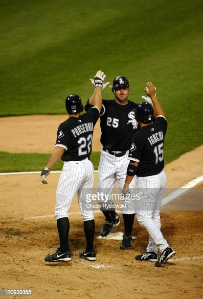 Chicago White Sox' DH/1B Jim Thomeis greeted at home plate by teammates Scott Podsednik and Tadahito Iguchi who scored ahead of his 3run homer into...